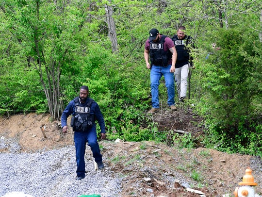 Law-enforcement personnel leave woods April 23, 2018, near the site where Travis Reinking, suspect in a mass shooting at a Waffle House in the southeast Nashville neighborhood of Antioch, was arrested.