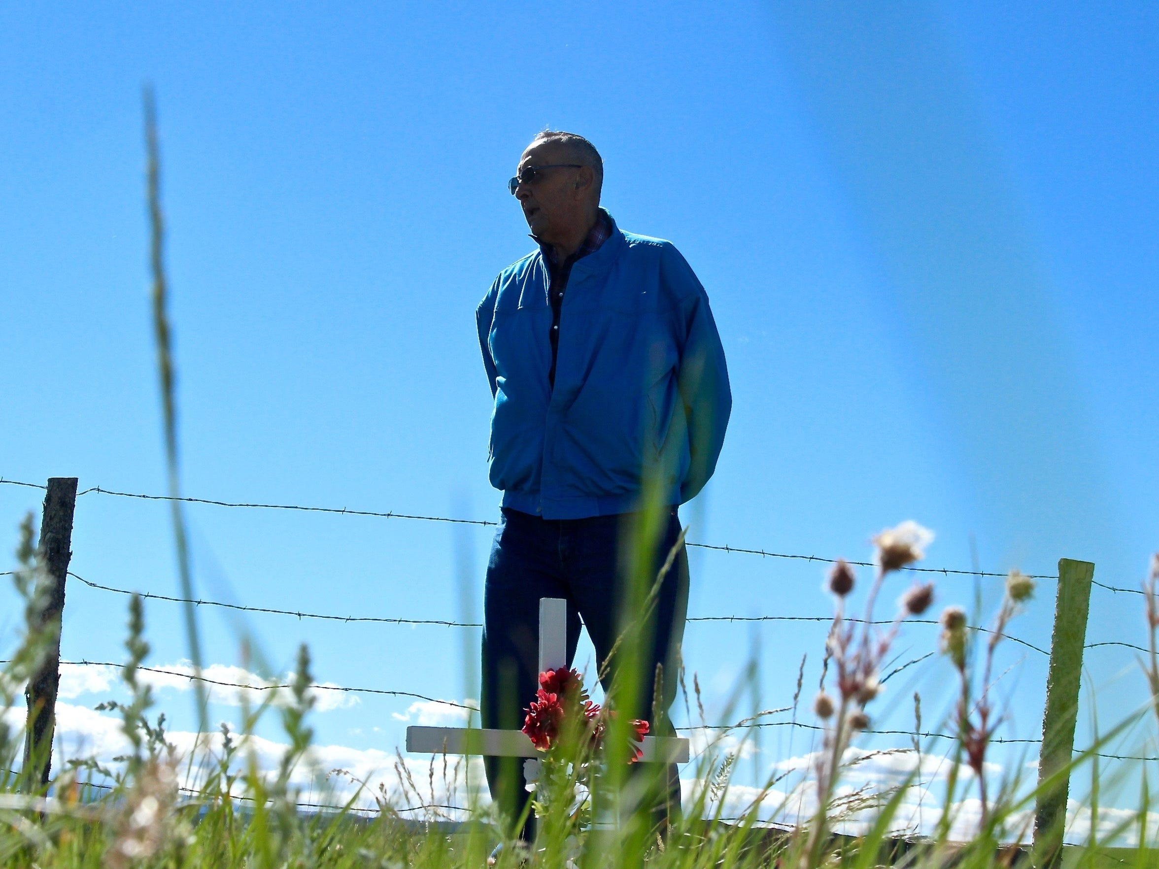 Dale Ell pauses at his family cemetery outside of Browning on the Blackfeet Indian Reservation. His Uncle, George Ell, will be reburied there Saturday after a 128-year absence