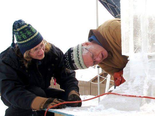 Wayne Miller of Walpole, N.H., eyes the base of his ice sculpture with his helper and wife Meg Kupiec.