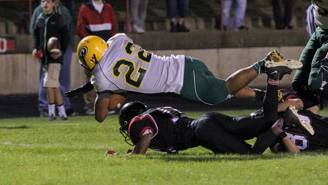 DeWan Smith of Pennfield goes over Marshall defenders and into the endzone.