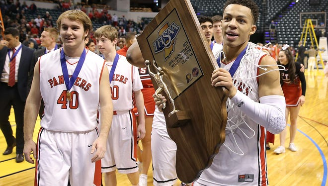 Park Tudor's Bryce Moore carries the 2A Championship trophy off of the court following their 73-46 win over the Frankton Eagles in the IHSAA 2A Boys Basketball State Final Saturday, March 28, 2015, afternoon at Bankers Life Fieldhouse.