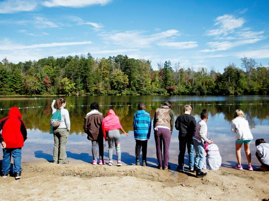 Claxton Elementary students look at small fish swimming in Lake Powhatan during their Muddy Sneakers lesson at Bent Creek October 11, 2016.