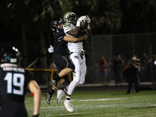 Nikki Liberal catches the ball as he's brought down by Adam Masterson during the Week 11 match up between Golden Gate and Gulf Coast at Gulf Coast High School on Friday, Nov. 3, 2017.
