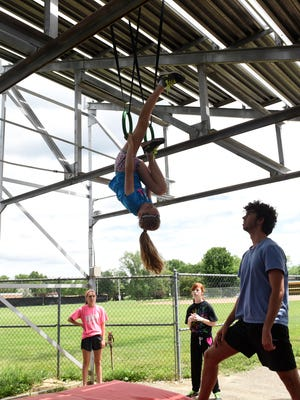 Hannah Chaney, an East Muskingum Local Schools eighth-grader participates in a swing drill Tuesday as Watkins Memorial graduate Chance Parson spots for her. Coaches and athletes from across the area traveled to Watkins Memorial High School to participate in their annual pole vault camp.