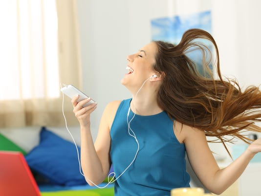 Teen listening music and dancing in her room