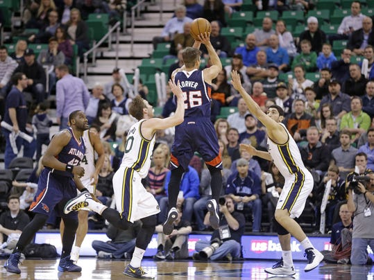 Atlanta Hawks' Kyle Korver (26) shoots as Utah Jazz's Gordon Hayward (20) and Enes Kanter, right, defend in the first quarter during an NBA basketball game Monday, March 10, 2014, in Salt Lake City. (AP Photo/Rick Bowmer)