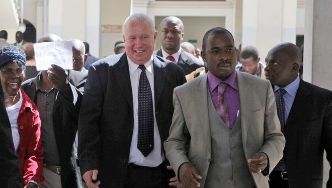 In this May, 10, 2010, file photo, Roy Bennett, center left, leaves the High Court in Harare, Zimbabwe, after he was acquitted of terrorism charges. New Mexico State Police said Thursday, Jan. 18 2018, that Zimbabwean opposition leader Roy Bennett died in helicopter crash. The crash on Wednesday, Jan. 17, carrying Bennett and five others went down in a mountainous rural area of northern New Mexico.