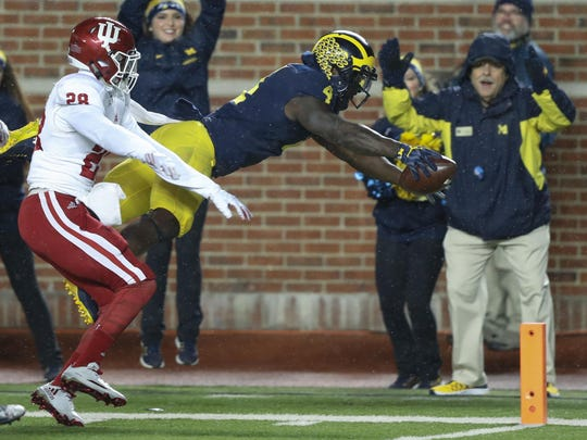 Michigan's De'Veon Smith dives into the end zone for a touchdown, beating Indiana's A'Shon Riggins, during the second half Saturday. Smith scored both U-M touchdowns.
