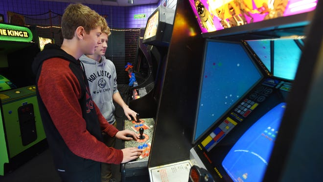 Ethan Shatz, left, and Austin Perry play a video game at Smashing Barrels in the Colony Square Mall.