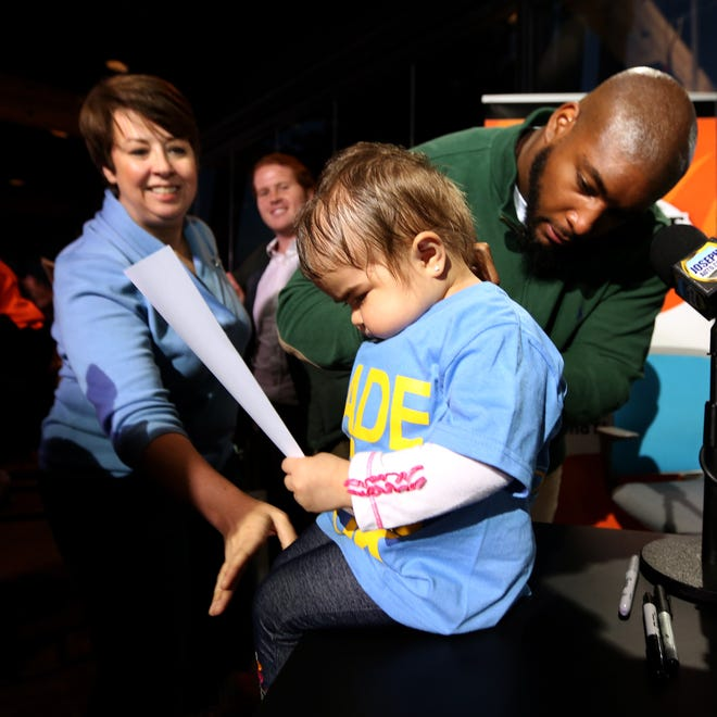Devon Still of the Bengals signs the shirt of Sophia Lopez, 4, of New York, as Ria Davidson, president and co-founder of the Dragonfly Foundation, watches. Sophia has Hemophagocytic lymphohistiocytosis (HLH) and is receiving treatment at Cincinnati Children's Hospital Medical Center.