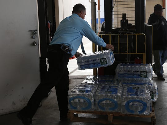 County Executive Officer Kim Carpenter loads water onto a forklift Wednesday while delivering items to the ECHO Food Bank in Farmington.
