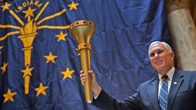 Gov. Mike Pence holds up the Indiana Bicentennial Torch, on Friday, Dec. 11, 2015, during the Statehood Day celebration at the Statehouse.  The celebration of Indiana's 199th birthday kicked off events leading to next year's bicentennial.