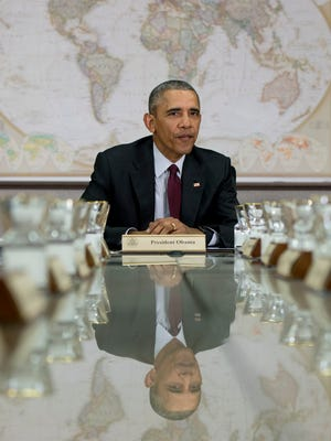 President Obama is reflected in the conference table before a meeting of his National Security Council at the State Department in Washington, Thursday.