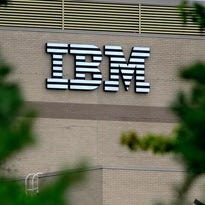 The classic IBM logo visible on the front of the Poughkeepsie main plant is viewed through a wall of trees along Spackenkill Road.
