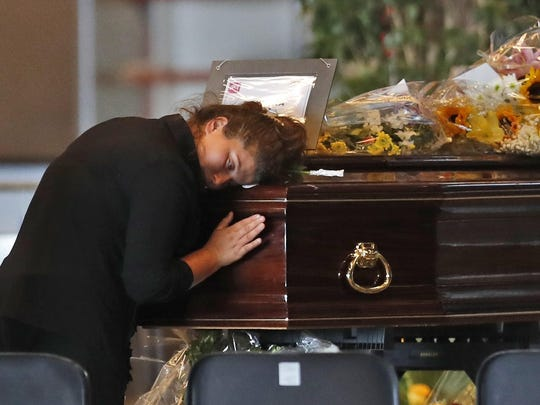 A woman mourns a victim of a collapsed highway bridge, at the Fiera di Genova exhibition center, where some of the coffins are laid in state, in Genoa, Italy, Friday, Aug. 17, 2018. A state funeral for most of the victims will take place in Genoa on Saturday.