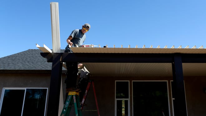 Jake Thrasher, of Lendman Construction, installs a patio cover on a new home in the Pleasant Hills subdivision in Anderson on Monday.