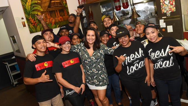 Pika Fejeran, owner and president of Pika's Cafe, poses with her staff for a group picture at her cafe in Upper Tumon on Nov. 28, 2016.