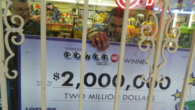 Benjamin Pendergrass, left, assists as Bobby Patel, owner of Wells Creek Market, put the big $2 million Lottery check in the window at the market back in 2015.