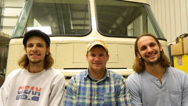 From left, Jordan Burgason of Burgie's, Steve Myers of Skunk River Restorations and Andrew Burgason of Burgie's sit on the front bumper of the 1958 Grumman Olson truck that is being converted into a coffee truck.