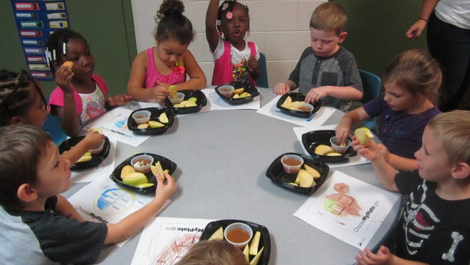 Students at Joseph H. Messina Children's Center in Fort Myers taste and learn about apples during a Food Literacy in Preschools, or FLIP, presentation by Community Cooperative. The organization's women's and children's programs are funded by the Becoming Cosmopolitan fundraiser, which takes place Thursday in downtown Fort Myers.