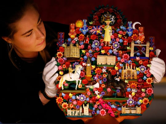 An employee of the Royal Collection Trust looks at the Tree of Life, a gift presented to Britain's Queen Elizabeth II from Mexican President Enrique Pena Nieto in 2015.