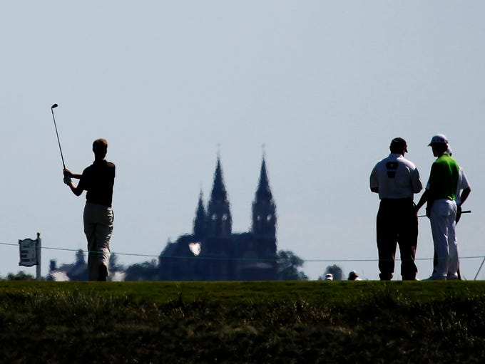Golfers are silhouetted on the sixth tee with a view