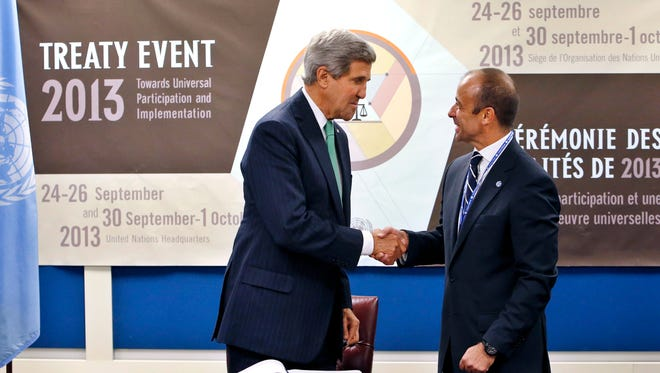 U.S. Secretary of State John Kerry, left, shakes hands with Under Secretary-General for Legal Affairs Miguel Serpa Soares after signing the Arms Trade Treaty during the 68th session of the United Nations General Assembly at U.N. headquarters, on Wednesday.