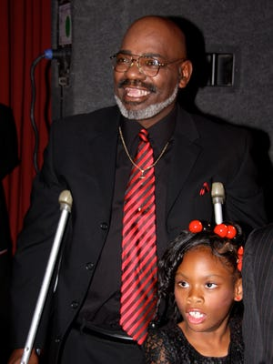 Anthony (Cass) Castelow flashes his trademark smile with his daughter, Myracle, after discussing faith at the Fox Theatre in 2009. He died this past week.