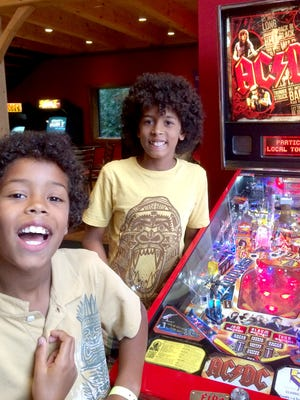 "Dominic Thomas, 9, left, and Sebastian Thomas, 12, brothers who live in South Burlington, play pinball Tuesday night at Tilt Classic Arcade and Ale House. ""I like the pinball machines and Pac-Man and how it's all sort of classic,"" Sebastian said."