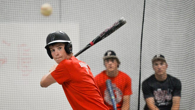 Pierz Pioneers senior Kolton Eischens takes batting practice Tuesday as his first cousins, juniors Brett Kapsner, center, and Lane Girtz, look on.