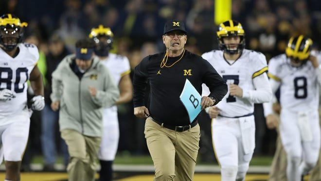 Michigan coach Jim Harbaugh warms up his team before action against Iowa Saturday in Iowa City, Iowa.