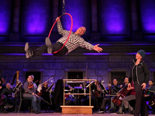 Rochester Philharmonic Conductor Jeff Tyzik, center, tries his hand at the aerial hoop under the eye of Cirque de la Symphonie performer Aloysia Gavre, far rght, during a rehearsal for the Cirque's performances tonight and tomorrow with the philharmonic.  Various acrobatic artists perform to music played behind them by the philharmonic.