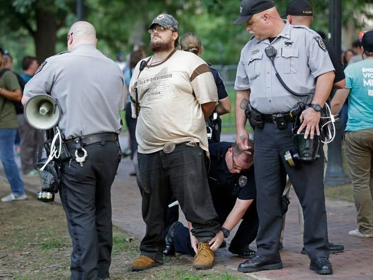 """Police arrest a man during a protest at a Confederate monument at the University of North Carolina in Chapel Hill, N.C., Tuesday, Aug. 22, 2017. The gathering Tuesday night at the university focused on a statue known as """"silent Sam."""" People chanted """"tear it down"""" while uniformed officers watched from behind temporary metal barriers ringing the statue, depicting a Confederate soldier."""