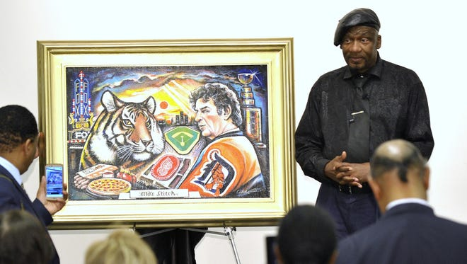 "Curtis Lewis II, right, and his wife, Cynthia Henley-Lewis, answer questions about ""Mr. I, Thanks for the Memories,"" a new painting honoring Mike Ilitch, at the Farmington Community Main Library on Wednesday. It is part of the exhibit ""The World Class Icon Collection."""