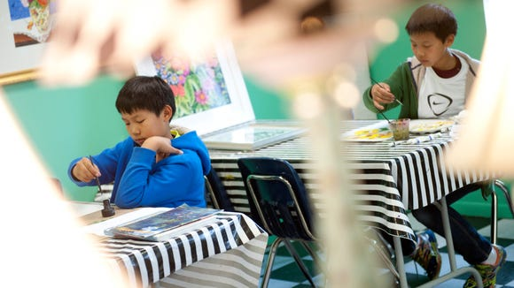 Max Boyang, 10, left, and his twin brother Louis work on paintings on Wednesday, May 4, 2016 at Arty Party Studio in Okemos. Art teacher Vivian Dwyer described Max's style of art as abstract with his use of patterns, while Louis enjoys painting flowers. They are having an art show at the studio from May 15- May 19. All proceeds will go to Joey's Wings Childhood Cancer Foundation.