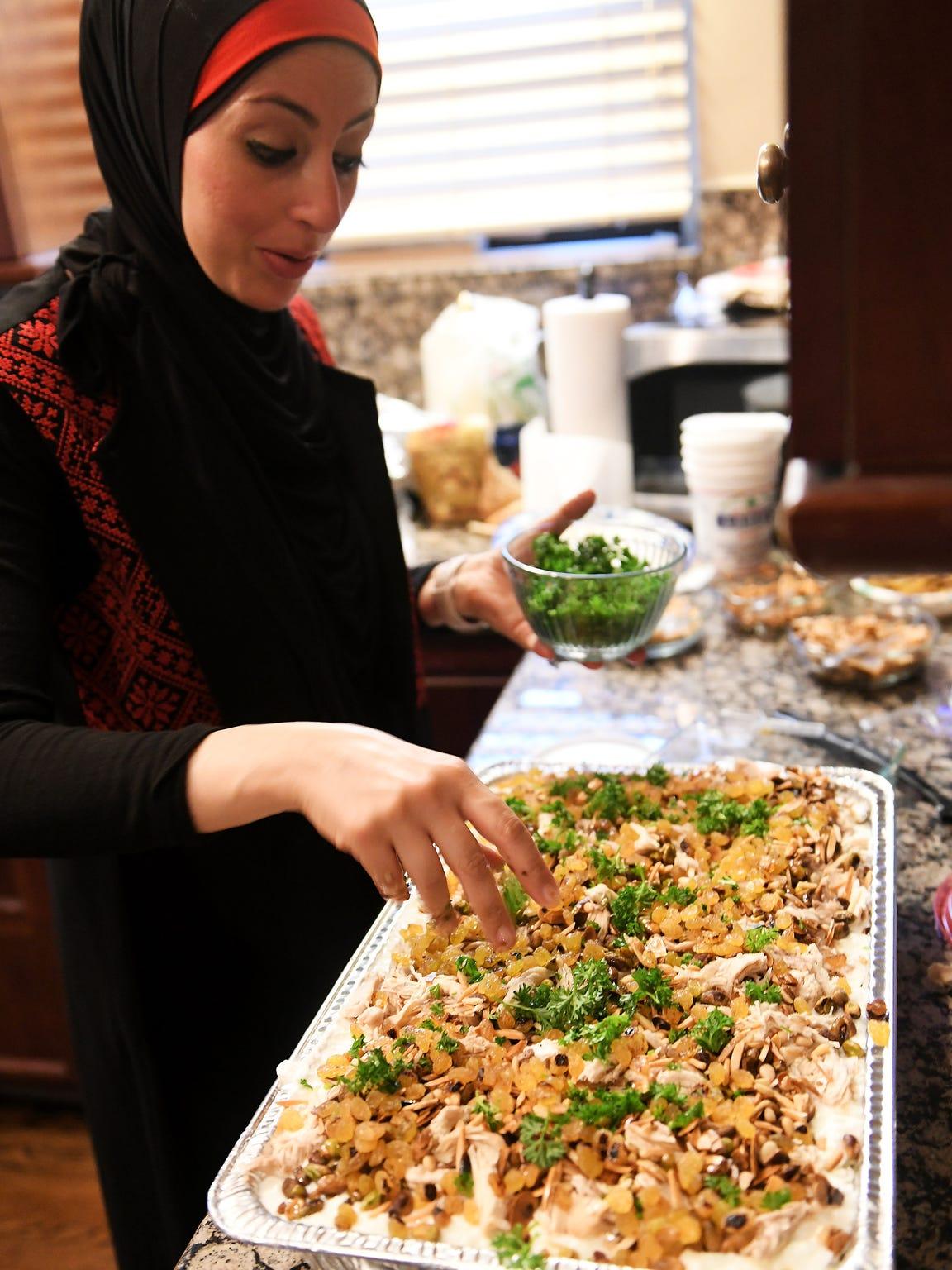 Ameena Elder, 34, sprinkles parsley on a platter of