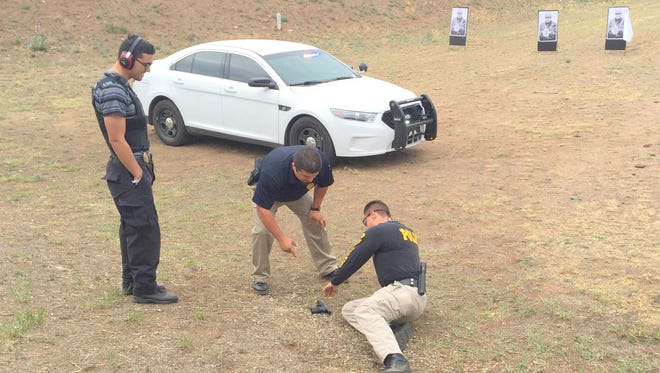 Bayard Police sergeant Joe Anthony Sierra does a stress type situational shooting drill with Captain Ricky Villalobos of the Silver City Police Department presiding. Santa Clara Police officer Oscar Pena looks on.