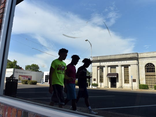 A group of youths walk through downtown Macon Thursday.