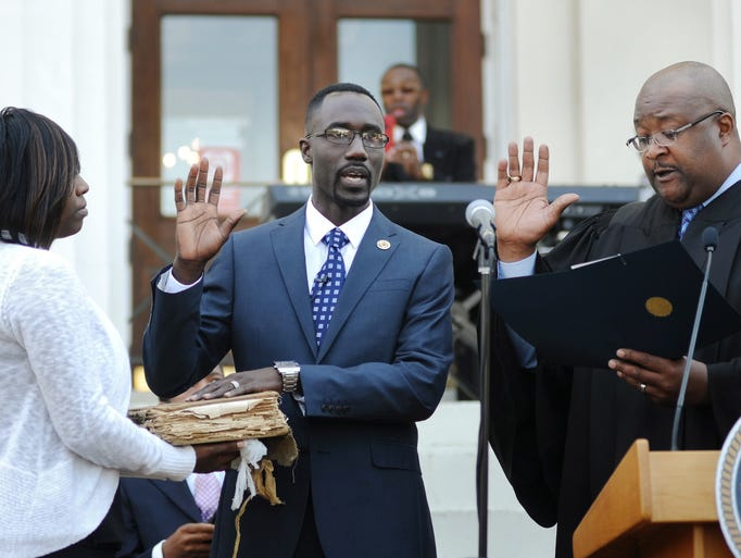 Tony Yarber is sworn-in as mayor of Jackson by Hinds County Justice Court Judge Frank Sutton as Yarber's wife, Rosalind Yarber looks on during a ceremony outside City Hall on Thursday.