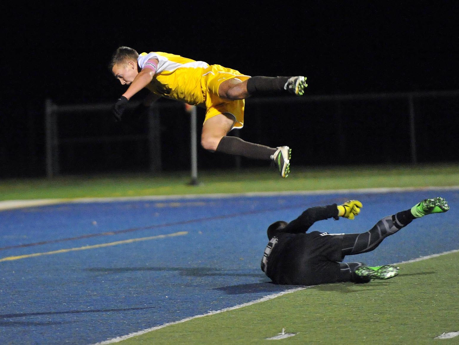 Delran's Michael Strohlein (left) is airborne after colliding with Holmdel goalkeeper Tyler Marchiano (right), while shooting in their Group 2 boys' soccer semifinal, Tuesday, Nov. 17 in Buena Vista.