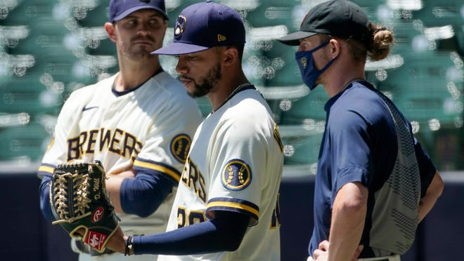 Milwaukee Brewers' Justin Grimm, Devin Williams and Josh Hader watch during a practice session Monday, July 13, 2020, at Miller Park in Milwaukee.