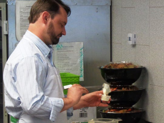Cory Partin, Tano's Bistro front room manager, does some food prep at Take Home Tano's where he'll work until Tano's Bistro in Historic Downtown Loveland.