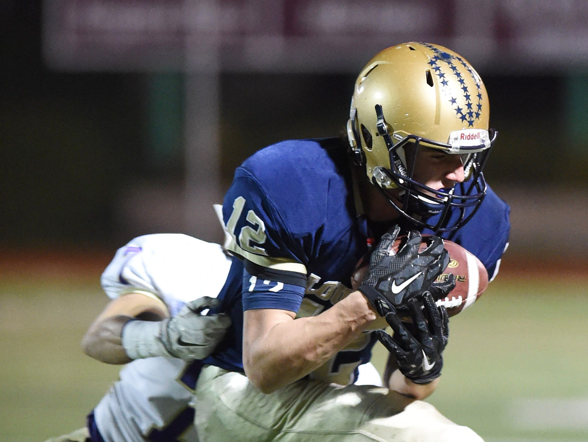 Lourdes' Luke Timm catches a pass ahead of Amsterdam's David Crawford during the Class A semi final at Dietz Stadium.
