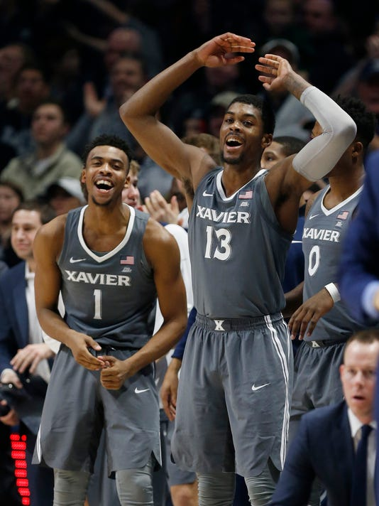 Xavier's Paul Scruggs (1) and Naji Marshall (13) cheer their team from the bench during the second half of an NCAA college basketball game against DePaul, Saturday, Dec. 30, 2017, in Cincinnati. (AP Photo/Gary Landers)