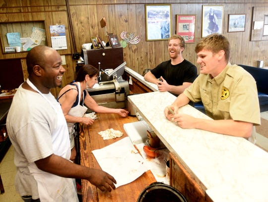 Shawn Feaster, left, laughs with customers at Cobb's