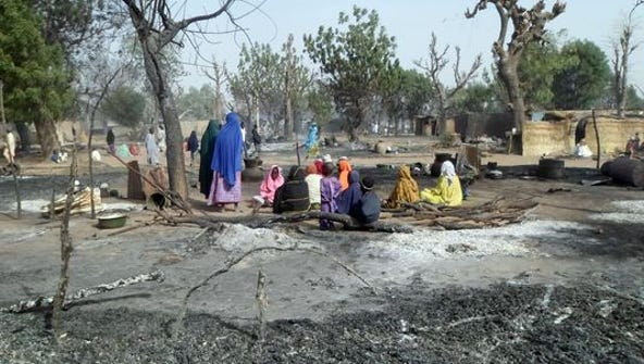 Women and children sit among burnt houses after Boko