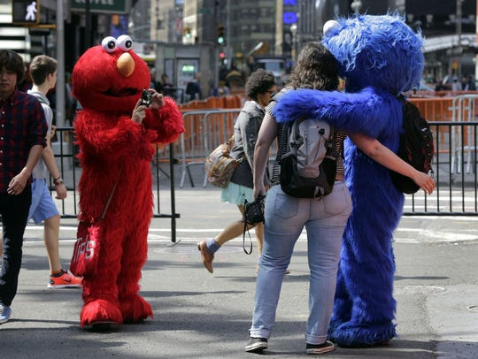 An Elmo character, left, uses a woman's camera to photographer