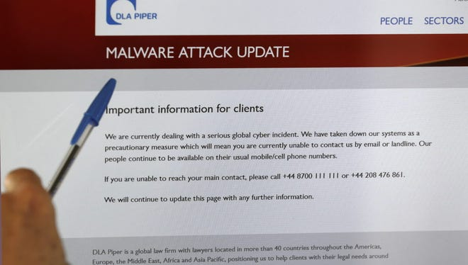 A screen displays the web site of the global law firm DLA Piper showing a message about a malware attack advising readers that their computer systems have been taken down as a precautionary measure due to what they describe as a serious global cyber incident, as seen from  Tasmania on June 28.