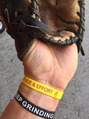 Mike Morris wears two bands on his left wrist. One says, Keep Grinding. The other says, Attitude and Effort.