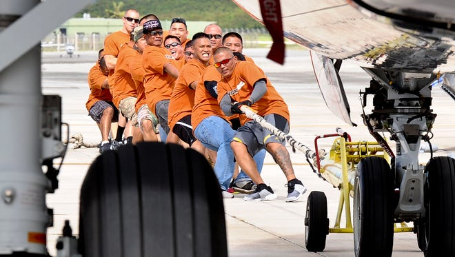 "in this file photo, members of the Guam Army National Guard 1st Battalion, 294th Infantry, do their best at the United ""Towing the Line to Save Lives"" Plane Pull."